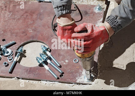 The builder rotates the nuts with an electric key. Screwing the bolts in the metal plate - Stock Photo