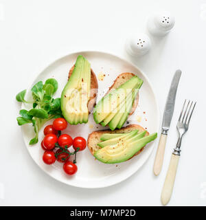 Avocado toasts, cherry tomatoes and salad on white plate, top view, square crop. Healthy lifestyle, vegen, vegetarian, - Stock Photo