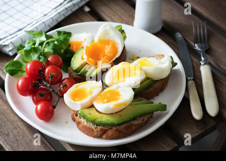 Egg and avocado, green salad and cherry tomatoes on white plate. Healthy breakfast, healthy lifestyle, vegan, vegetarian - Stock Photo