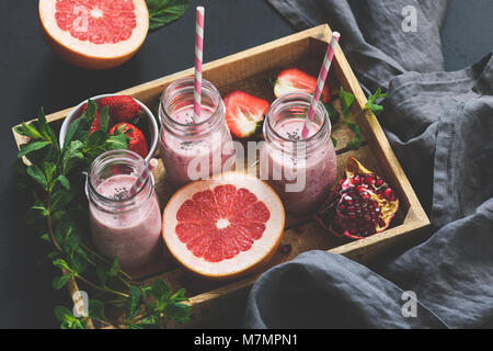 Pink fruit smoothies in bottle. Grapefruit, pomegranate and strawberry smoothies. Toned image, selective focus. - Stock Photo