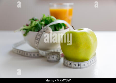 Measuring tape around the apple, bowl of green salad and glass of juice. Weight loss and right nutrition concept - Stock Photo