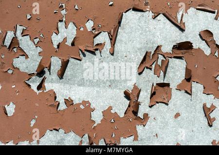old peeling flaking paint on zinc coated, galvanized metal panel - Stock Photo