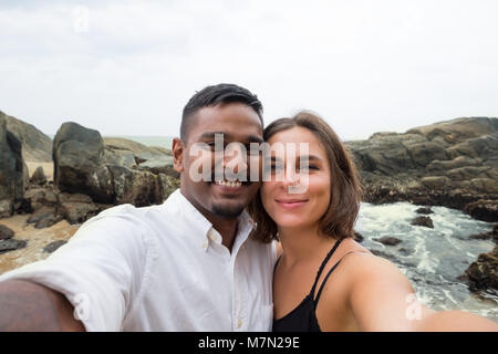 Young caucasian woman and asian man making selfie during honey moon in Sri lanka on beach - Stock Photo