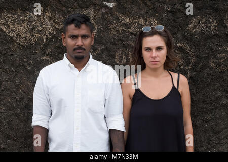 Emotional portrait of young just married couple. They stand near the wall and look on camera - Stock Photo