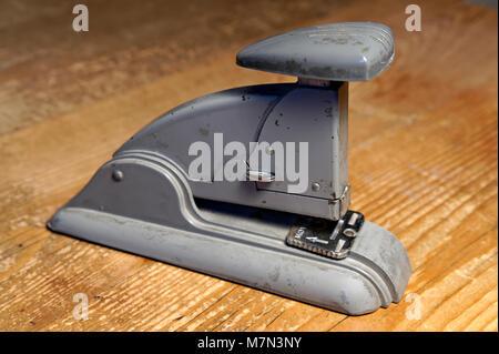 Vintage 1940's era Swingline Speed Stapler sitting on an old wooden desk - Stock Photo