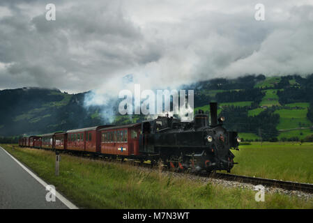 Retro locomotive with smoking engine moving forward in Alps mountains. Scenic view on vintage train against forest - Stock Photo