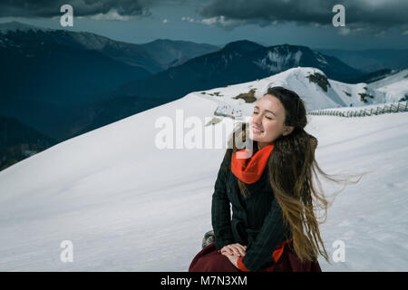 Young woman sits on the top of snowy mountains in the ski resort. Trendy traveler enjoys wonderful day and takes - Stock Photo