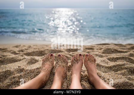 Travel concept. Scenic view from beach on sea and sky. Two girls are sunbathing on sand. Close-up view on pair of - Stock Photo