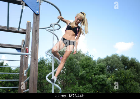 Athletic young woman doing sports in park. Slim blonde girl with beautiful hair engaged in fitness. Attractive female - Stock Photo