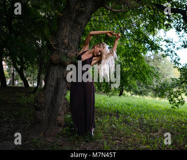 Young shapely woman stands under the big tree in city park. Slim blonde girl with beautiful hair in dress is posing - Stock Photo