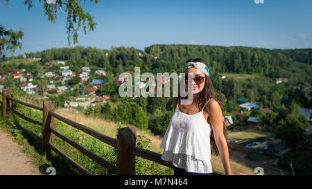 Young woman in sunglass and bandage stands near fence on hill in summer day. Girl standing in park on background - Stock Photo