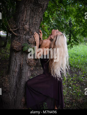Young shapely woman stands under big tree and relaxes in the park. Slim blonde girl with beautiful hair in dress - Stock Photo