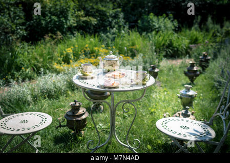Tea ceremony at the green garden in the courtyard of the house. Kettle with coffee or tea with two cups and sweets - Stock Photo