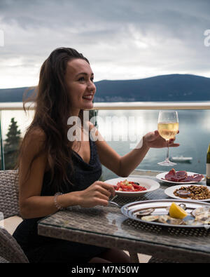 Young happy woman sits on balcony at table with oysters, meat and salad and holds glass of sparkling wine. Elegant - Stock Photo