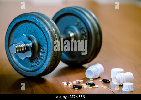 Steroid pills and capsules with dumbbell weight in the background - doping in sport. - Stock Photo