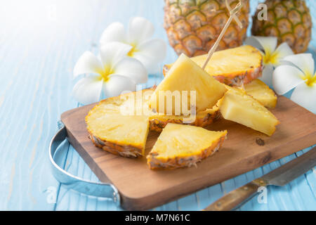 fresh sliced pineapple on wood block and blue wood background, summer fruits concept - Stock Photo
