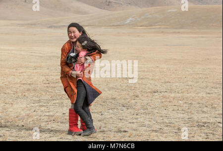 Hatgal, Mongolia, 3rd March 2018: nomad girls in a steppe of northern Mongolia trying to hide from a dust storm - Stock Photo