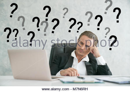 rear view of a caucasian business person looking at the question marks on white board. - Stock Photo