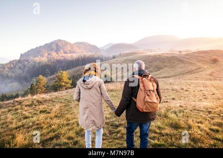 Senior couple on a walk in an autumn nature. - Stock Photo
