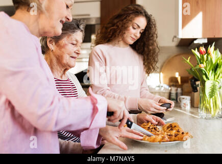 A teenage girl with mother and grandmother at home. - Stock Photo
