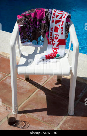 Six Nations rugby union England v Italy scarf hanging over a chair by a swimming pool with an almost empty glass - Stock Photo