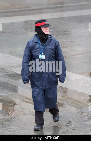 Piccadilly circus, London, UK. 12th Mar, 2018. Heritage warden wearing a waterproof coat on a dull, wet and miserable - Stock Photo