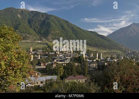Historic tower houses amidst modern buildings on a hillside in Mestia, Svaneti region of the Caucasus, Georgia - Stock Photo
