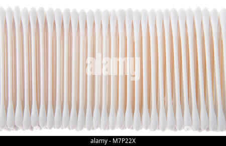 cotton swabs on sticks stacked and lined up in a row. Isolated on white background. commonly used in a variety of - Stock Photo