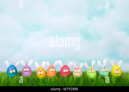 Colorful decorated Easter Eggs with bunny faces and ears lined up in a row on green grass, vintage sky background. - Stock Photo