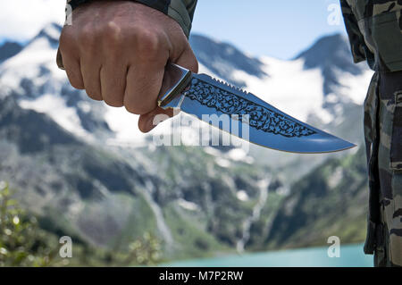 Adventure wilderness nature man with knife in camouflage pants, outdoor lifestyle survival concept. Unrecognizable - Stock Photo