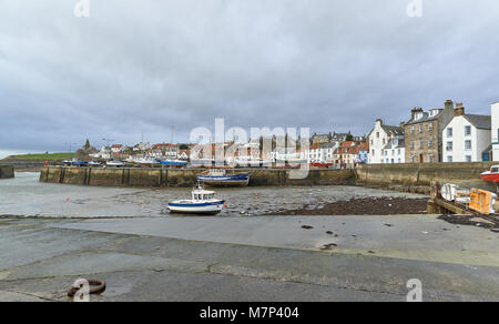 St Monans harbour on a Wet, Windy Winters day one January. The Old Fishing Boats aground on the Mud during the low - Stock Photo