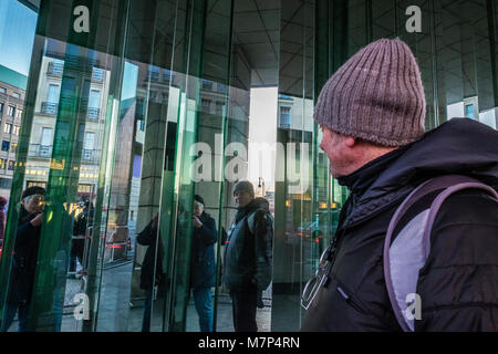 Berlin-Mitte.Elderly tourists taking photos of themselves in reflective building surface.Senior man & woman take - Stock Photo