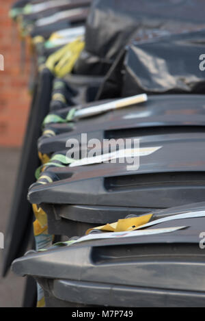 row of wheelie bins in the UK with brick wall in background - Stock Photo