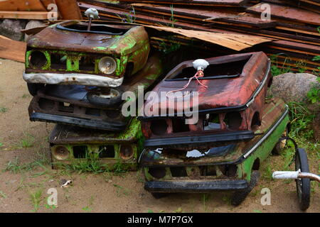 Old colorful green and red toy car wrecks in a pile - Stock Photo