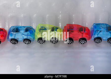 transparent coloured toy cars stuck in ice and snow - Stock Photo