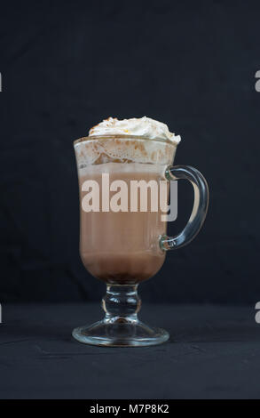 On a black background mug of hot cocoa with cream. - Stock Photo
