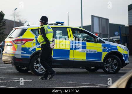 policeman with arms behind his back and hands clasped walks in front of police car - Stock Photo
