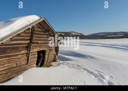 Old timbered barn with a pair of ski leaning against it and a blue sky and moutains in background, picture from - Stock Photo