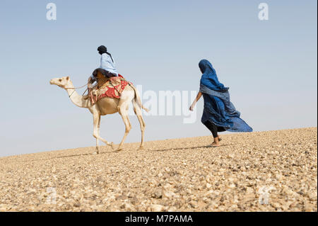 Woman walking behind a man riding on a camel in Mauritania,Western Sahara Desert. - Stock Photo