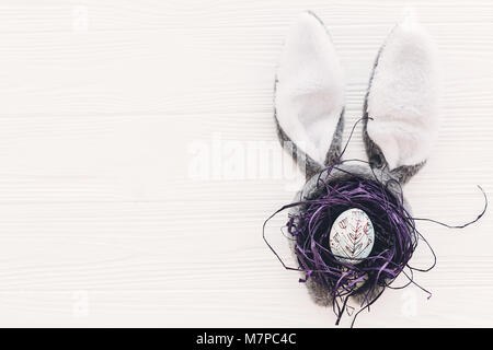 happy easter concept. bunny ears and stylish egg in nest on white wooden background flat lay with space for text. - Stock Photo