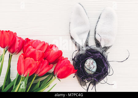 happy easter concept. bunny ears and stylish egg in nest  and tulips on white wooden background flat lay with space - Stock Photo