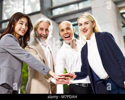 caucasian asian latino corporate business people putting hands together showing unity and team spirit - Stock Photo