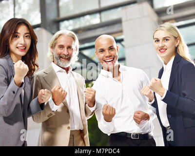 caucasian asian latino corporate business people making a fist showing determination and team spirit - Stock Photo
