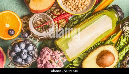 Green smoothie beverage in bottle with various healthy vegan ingredients: orange,blueberries,avocado, top view. - Stock Photo
