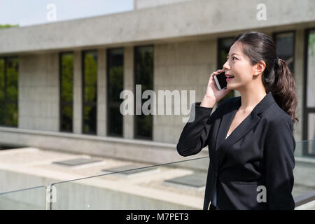 Portrait of a businesswoman in office formal dress talking with the customer on the cell phone outside. - Stock Photo
