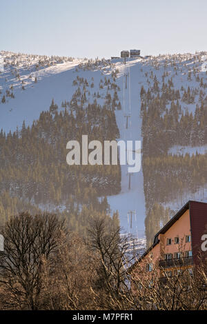 Ski lift to the top of Kopa mountain on a sunny winter day as seen from Karpacz ski resort, Poland - Stock Photo