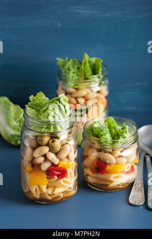 vegan couscous and pasta salad in mason jars with vegetables beans - Stock Photo