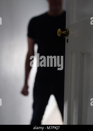 Threatening man in doorway at home with a clenched fist. Domestic violence. - Stock Photo