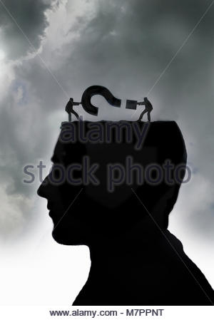 Man struggling with question mark inside of head - Stock Photo