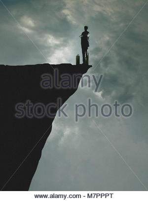 Businessman checking the time waiting at the edge of a cliff - Stock Photo